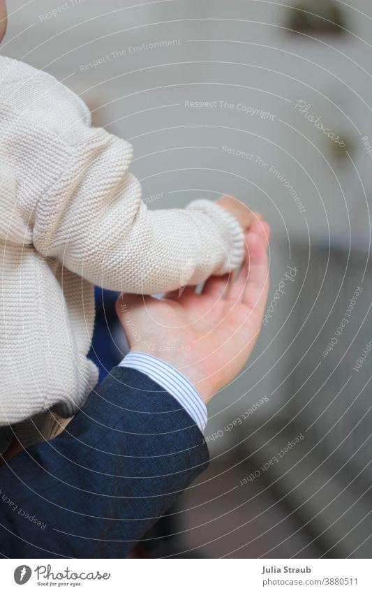 Hand in Hand Vertrauen schenken Kinderhand beschützend haltend Kindergarten Erwachsener Mann Strickjacke beige Hemd Anzugjacke Rückansicht Hände Stützen