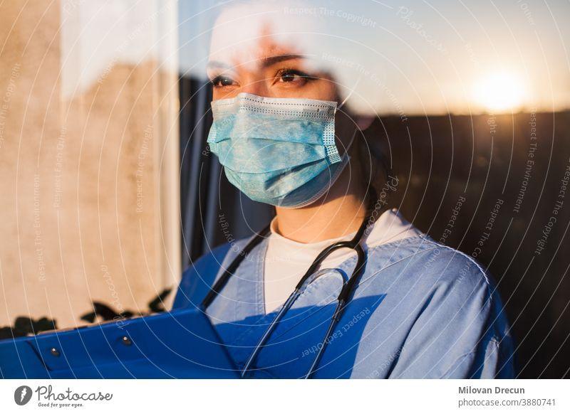 Junger Arzt schaut durch das Fenster Anspannung Pflege Klinik betroffen Korona Coronavirus COVID Kur niedergeschlagen Diagnostik älter emotional Gerät Gesicht