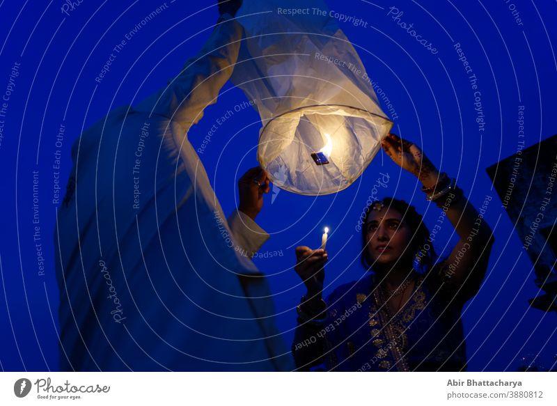 Ein indisch-bengalisches Ehepaar feiert Diwali, indem es in der blauen Stunde fliegende Laternen am Himmel anzündet. Indischer Lebensstil und Diwali-Feier