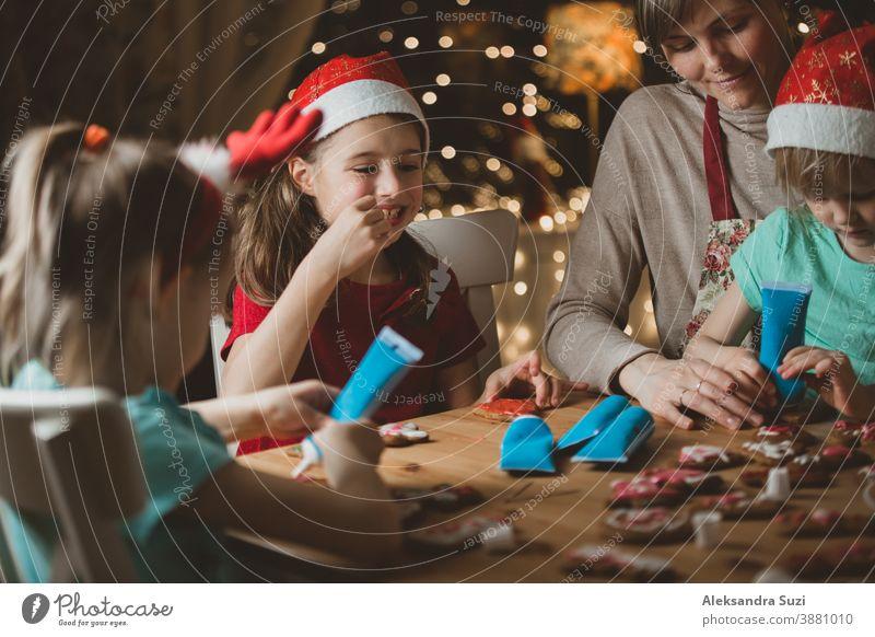 Mutter und kleine Kinder mit roten Hüten, die Lebkuchen backen und mit Glasur dekorieren. Wunderschönes Wohnzimmer mit Lichtern und Weihnachtsbaum. Fröhliche Familie, die gemeinsam Feiertage feiert.