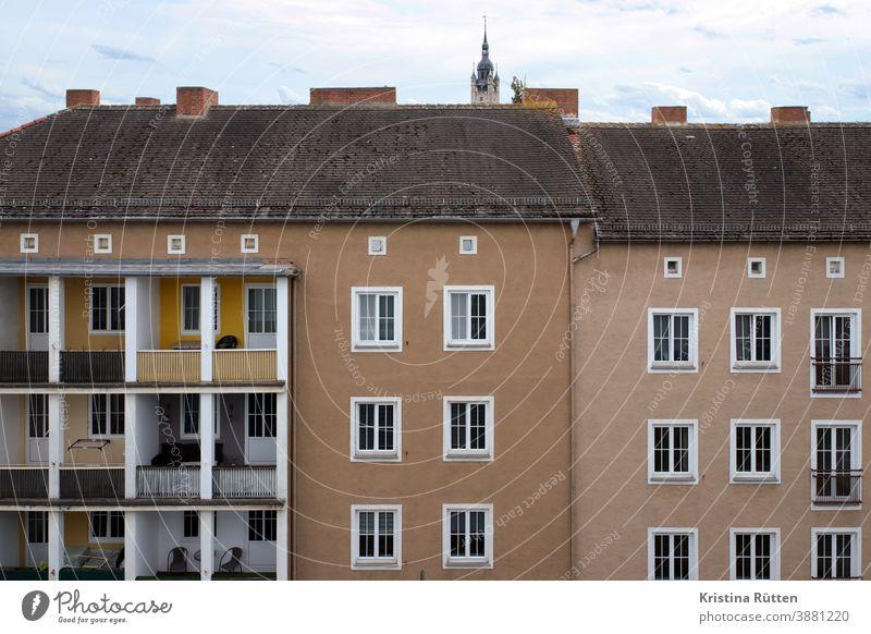 mehrfamilienhäuser mit und ohne balkone haus wohnhaus gebäude architektur fassade loggia loggien kirchturmspitze mehrfamilienhaus wohnblock wohnungen mietshaus