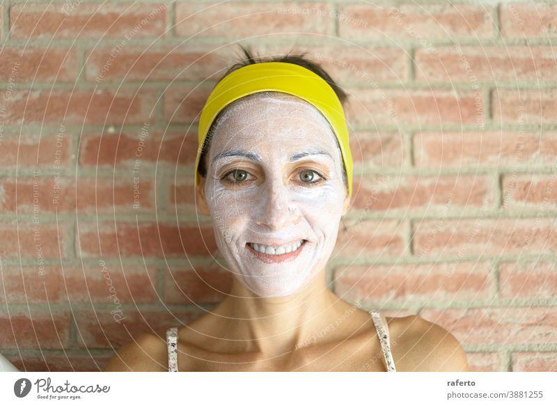 Entspannte Frau trägt zur Verjüngung eine Mineral-Ton-Maske auf das Gesicht auf und trägt ein Stirnband am Kopf Hautpflege Mundschutz Kosmetik Pflege