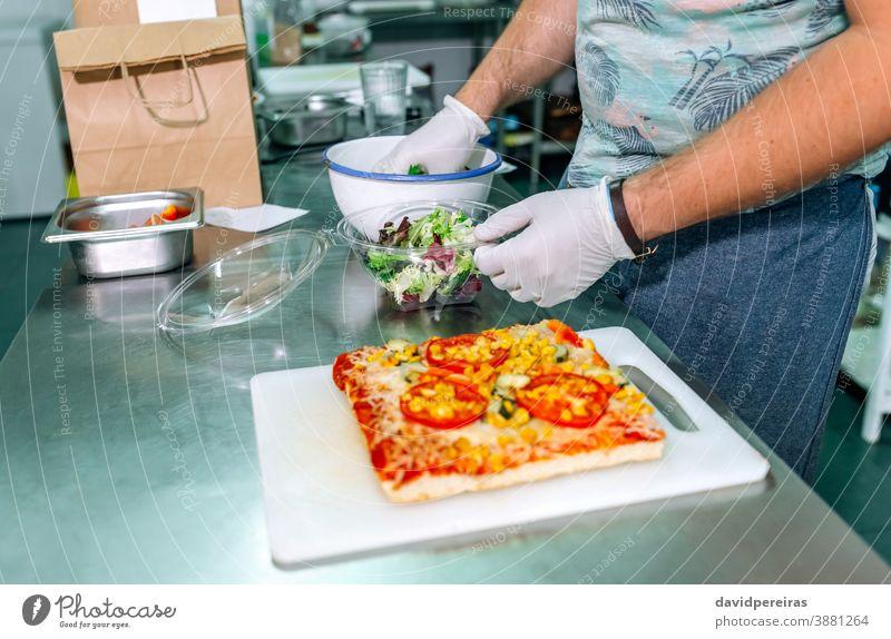 Unbekannter Koch bereitet Takeaway-Bestellungen vor unkenntlich Orden Imbissbude Verpackung Salatbeilage Handschuhe Hygiene sichere Lebensmittel Großküche Paket