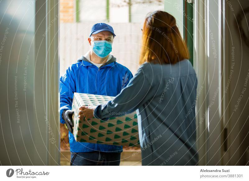 Zusteller bringt Urlaubspakete. Frau zu Hause steht in der Tür und nimmt Pakete für Weihnachtsgeschenke entgegen. Zusteller mit Schutzmaske und Handschuhen.