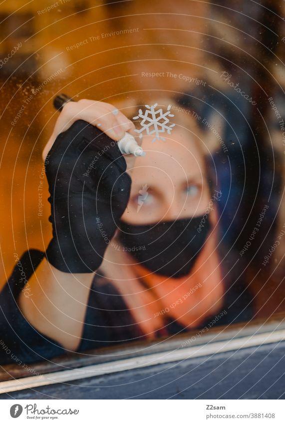 Illustratorin bei der Weihnachtsbemalung einer Fensterscheibe illustration window painting malen stift schneeflocke weihnachten künstlerin corona maske pandemie