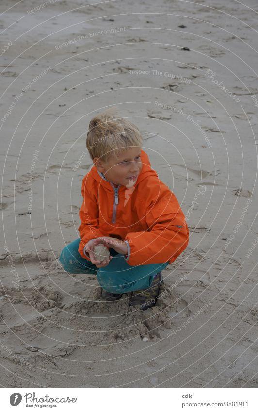 sandige Angelegenheit Junge blond in der Hocke im Sand am Meer orange Windjacke türkis Ferien Sandkugel formend beobachtend