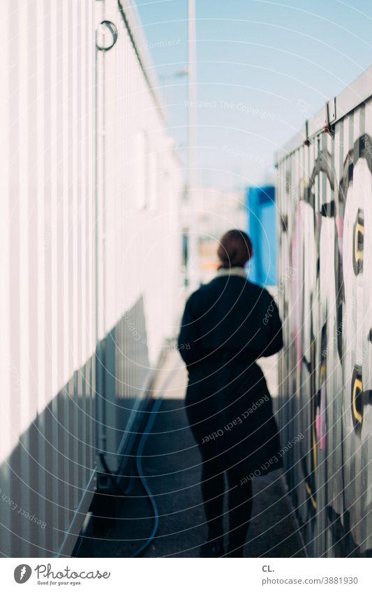 zwischen containern Container Frau Rückansicht anonym Identität Graffiti geheimnisvoll Bewegung gehen verfolgen allein Wege & Pfade draußen unscharf