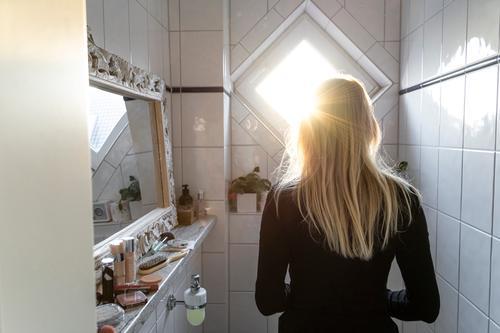 Rückansicht einer Blonden Frau, die in Bad steht blond Gegenlicht Badezimmer Sonnenlicht Pflege Hygiene im Innenbereich Fliesen u. Kacheln Farbfoto