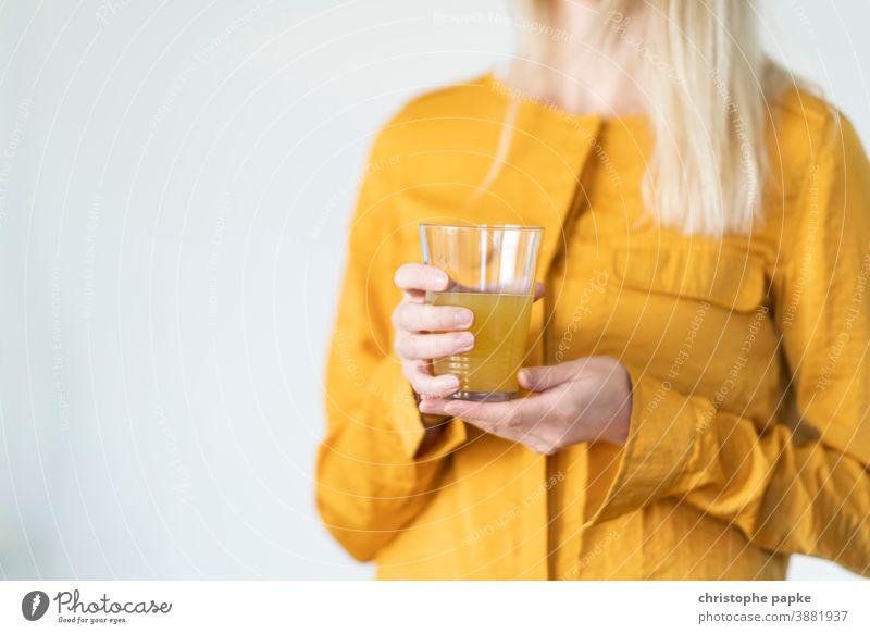 Blonde Frau hält Glas mit Limonade blond Orangensaft trinken Trinkglas halten orange Getränk Saft Erfrischungsgetränk lecker gelb süß Farbfoto Sommer