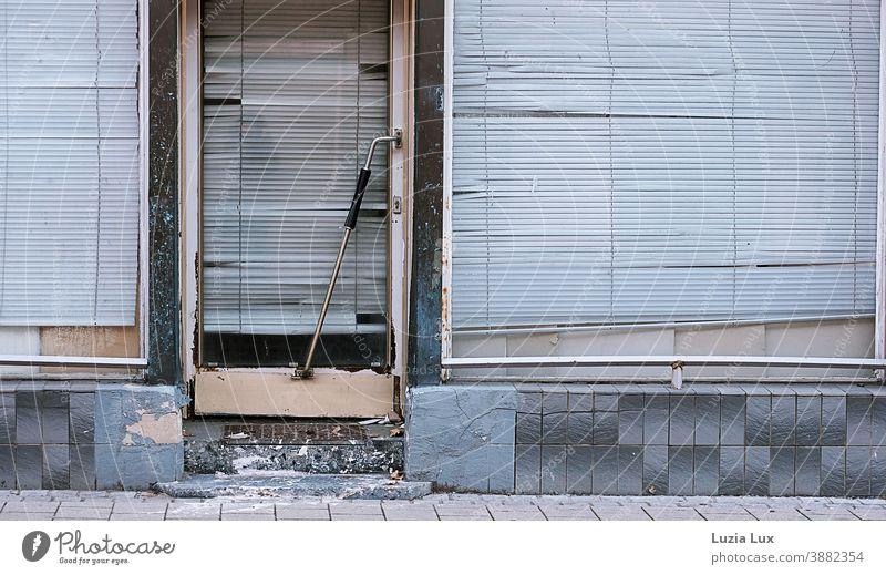 Geschlossen: Straßenansicht eines schon lange geschlossenen Ladengeschäfts mit zerfallenden Eingangsstufen und heruntergelassenen, schiefen Rollos alt baufällig