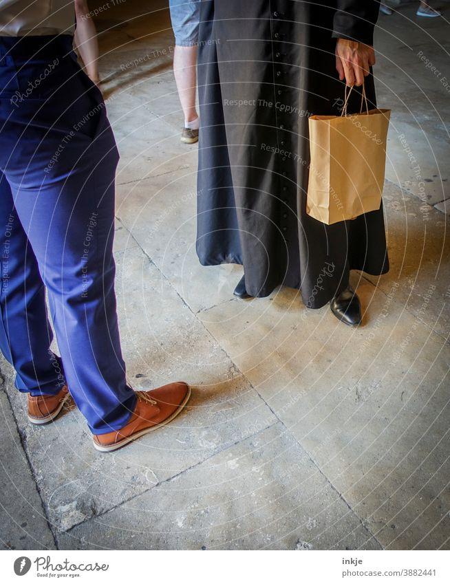 Mann in Talar mit Papiertasche und Mann in Stoffhose stehen sich gegenüber Farbfoto Menschen Hose Schuhe Gespräch Kommunikation Geistlicher Unterhaltung