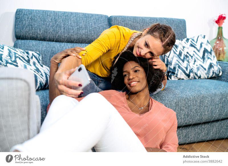 Glücklich diverse Freundinnen nehmen Selfie zu Hause Frauen Paar kuscheln sich[Akk] entspannen lesbisch Zusammensein Partnerschaft Smartphone Telefon
