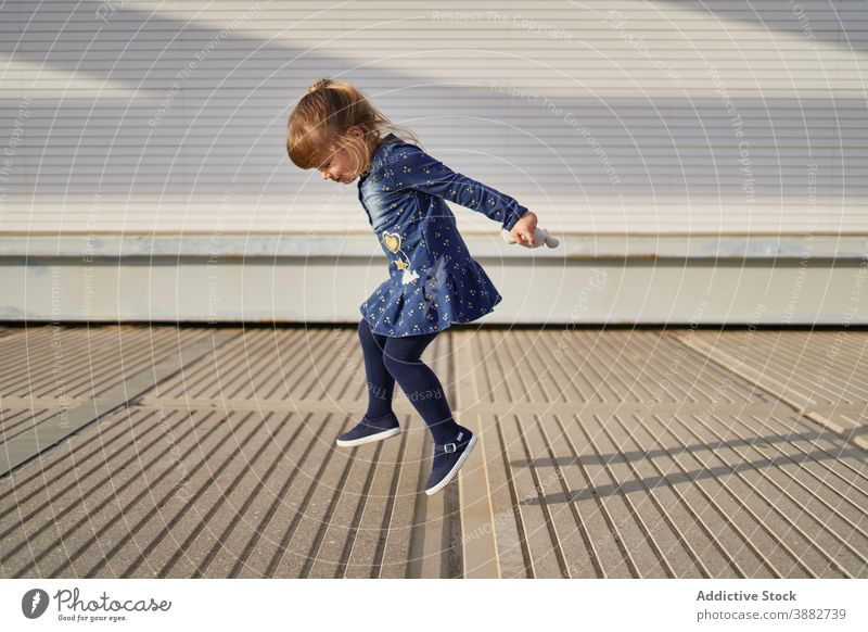 Glückliches Mädchen springt auf der Straße springen Kind Sprung sorgenfrei Spaß haben spielen lustig spielerisch heiter unterhalten Spiel Wochenende Großstadt