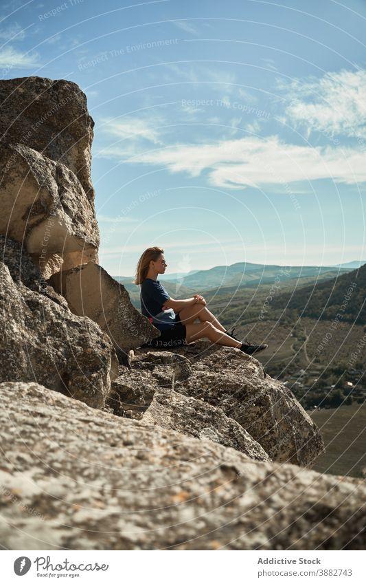 Reisende Frau sitzt auf einem Felsen im Hochland Wanderer Berge u. Gebirge Trekking Aussichtspunkt sich[Akk] entspannen Freiheit genießen Hügel felsig Abenteuer