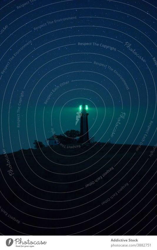 Leuchtturm leuchtet in der Nacht gegen Sternenhimmel glühen Licht Leuchtfeuer sternenklar Himmel Hügel Turm leuchten grün Landschaft Natur malerisch Dämmerung