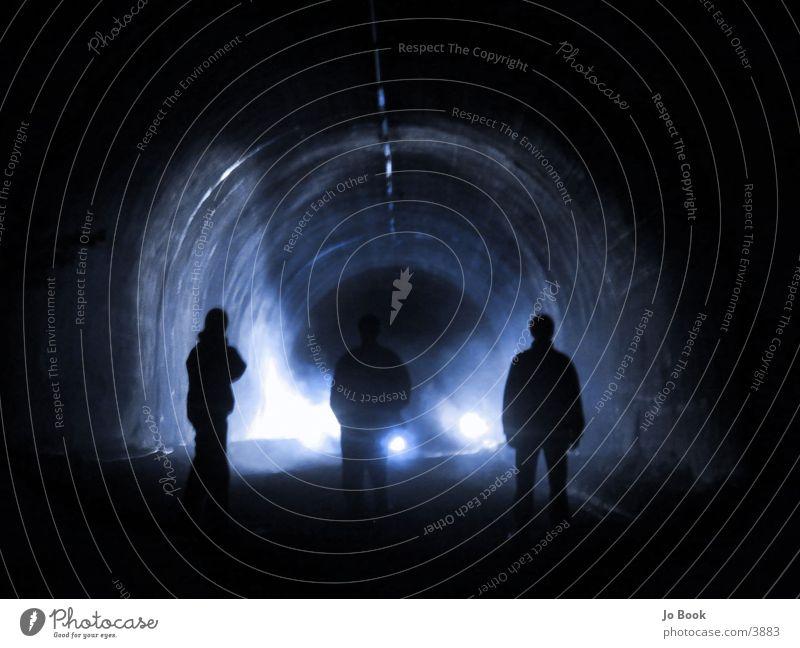 Tunnel Scherenschnitt Silhouette Menschengruppe Scheinwerfer blau 3 Menschen