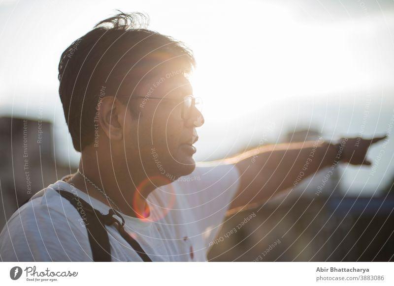 Nahaufnahme des Porträts eines indischen Bengalis mittleren Alters mit Brille in lässiger Stimmung auf dem Dach, mit der Sonne im Rücken als flackerndem Lichtpunkt. Indischer Lebensstil