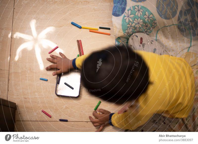 Ein indisch-bengalischer kleiner Junge, der an einem Ferienmorgen zu Hause mit Farbstiften/Skizze spielt. Indischer Lebensstil Asien asiatisch Baby schön