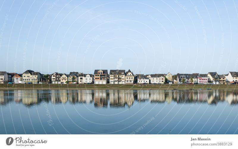 Spiegelung einer Kleinstadt im Fluss Haus Wasser Boot Himmel blau Stadt Dorf Häuserzeile Tourismus Reflexion & Spiegelung Gebäude Fassade Architektur Dach