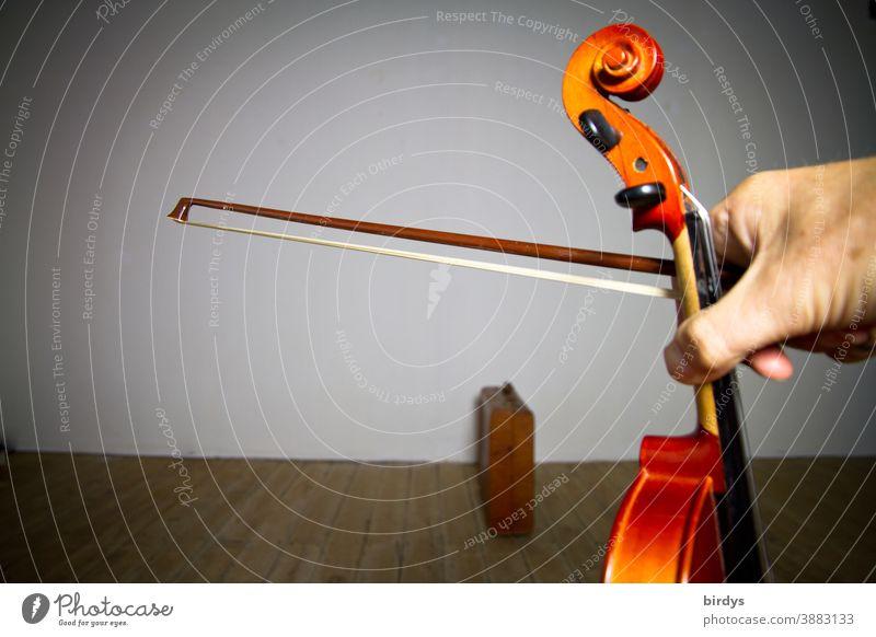 Geige und Bogen in der Hand des Musikers in einem leeren Raum. Auftrittsverbot in der Coronakrise Geigenbogen leerer Raum allein Künstler Musikinstrument