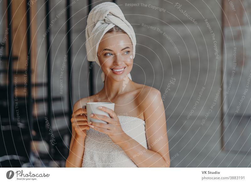 Attraktive junge Frau trägt nach dem Duschen Feuchtigkeitscreme auf das Gesicht auf, lächelt breit, in Handtücher gehüllt, trinkt Kaffee, posiert drinnen, denkt an etwas Angenehmes. Konzept der Schönheitspflege