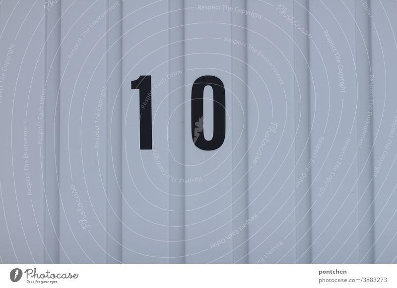 Zehn, volle Punktzahl. Die schwarze Zahl zehn auf einem Garagentor. Nummerierung, Zuordnung markierung garage garagentor geschlossen zuordnung Einfahrt trist