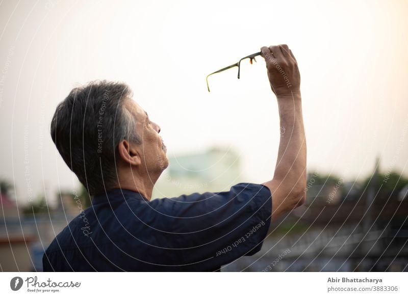 Ein alter indisch-bengalischer Mann in blauem Hemd hält seine Brille in die Luft, um sie aufmerksam zu beobachten, während er auf einem Dach unter freiem Himmel steht. Indischer Lebensstil und Senioren