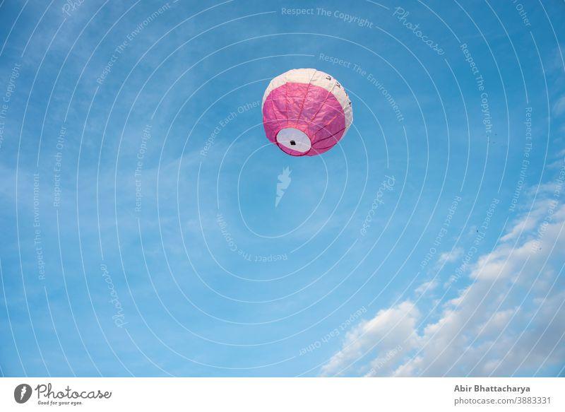 Eine bunte Laterne/Ballon fliegt am Nachmittag von Diwali am blauen Himmel mit weißen Wolken. Indisches Fest Abenteuer Air Asien Hintergrund Luftballon schön