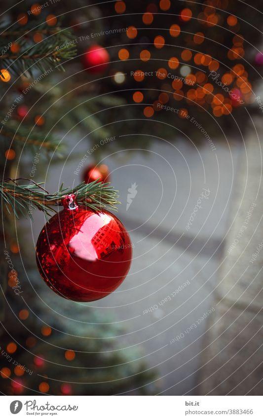 Rote Christbaumkugel, hängt am Weihnachtsbaum, auf Weihnachtsmarkt, vor glänzendem Bokeh. Weihnachten & Advent Weihnachtsdekoration Weihnachtsbeleuchtung