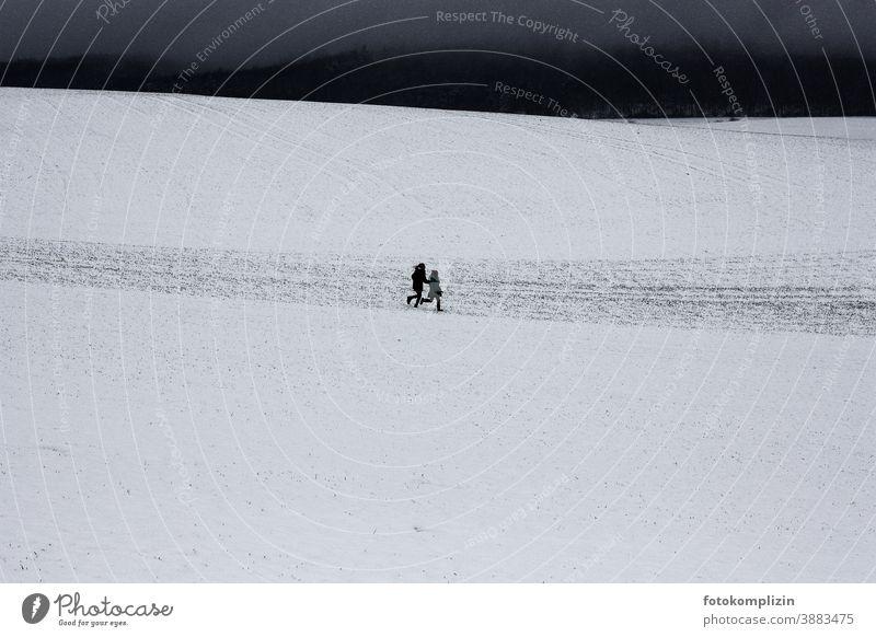 zwei Kinder laufen über ein verschneites Feld gemeinsam erleben Kindheitserinnerung Gemeinsame Basis zur gleichen Zeit springen rennen Glück Winterferien