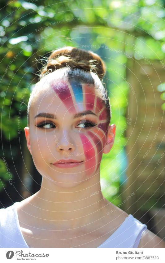 Schöne junge Frau mit einem Make-up in Form eines mehrfarbigen Sonnenstrahls. Brötchenfrisur, blondes und hellrotes Haar. Mädchen mit falschen Wimpern an den Augen und mit einem schelmischen Blick.