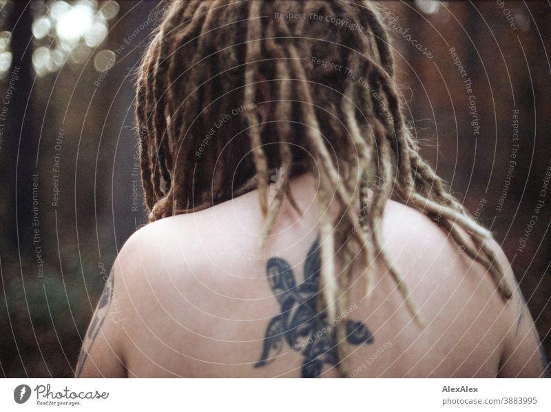 Rückwärtiges Portrait einer jungen Frau mit Dreadlocks und Tätowierungen im Wald dunkelblond Schmuck Piercing Ohrring verdeckt direkt nahe Haut Ausdruck groß