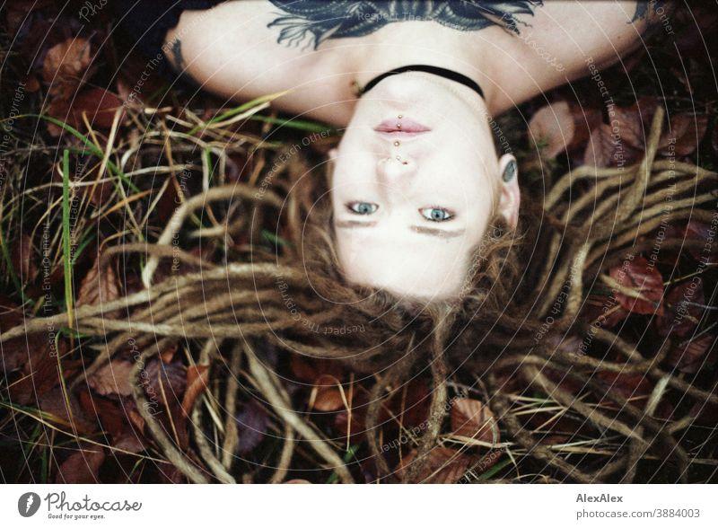 Portrait einer jungen Frau mit Dreadlocks und Tätowierungen auf dem Waldboden im Herbst dunkelblond Schmuck Piercing Ohrring verdeckt direkt nahe Haut Ausdruck