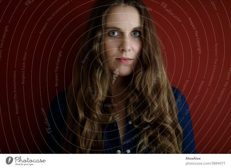 Portrait einer jungen Frau vor einer roten Wand schlank schön brünett lange Haare Gesicht schlau emotional sehen schauen Blick direkt natürlich hellhäutig blass
