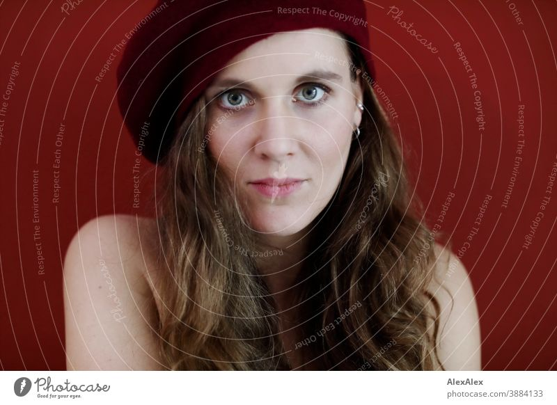 Portrait einer jungen Frau mit Hut vor einer roten Wand schlank schön brünett lange Haare Gesicht schlau emotional sehen schauen Blick direkt natürlich