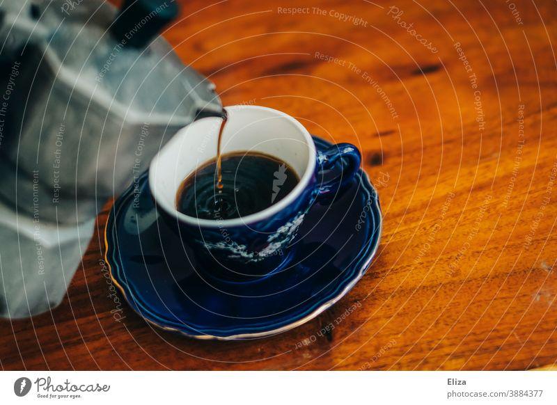 Kaffee wird aus einer Herdkanne in eine Tasse gegossen Bialetti kaffee eingießen Espresso Espressokocher frisch gebrüht Kaffeetrinken Espressotasse Kaffeetasse