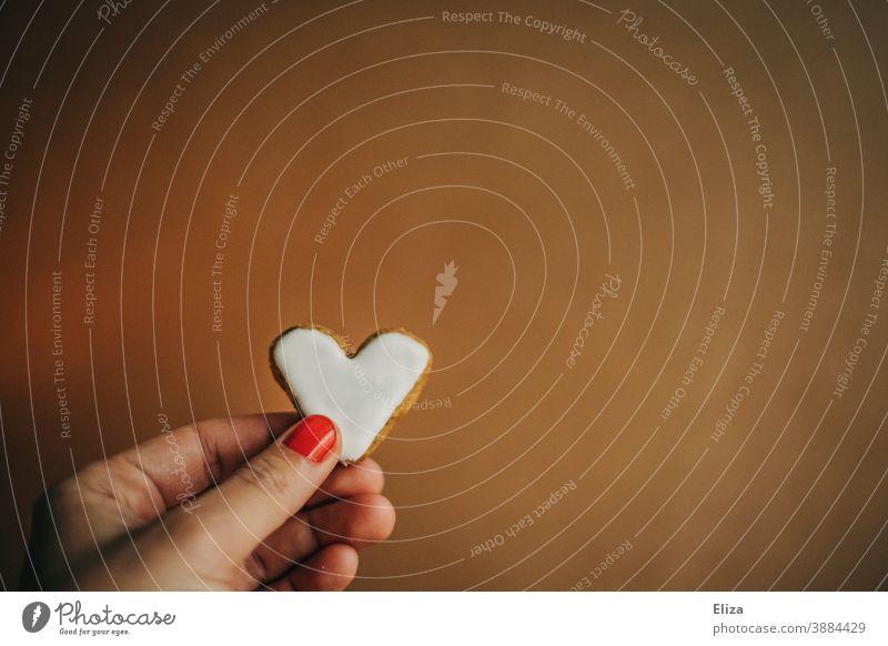 Weibliche Hand hält ein herzförmiges Plätzchen mit weißem Zuckerguss zum Valentinstag oder Muttertag Keks Herz Liebe lecker süß naschen Süßwaren Backwaren braun