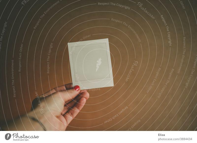 Eine weibliche Hand hält ein leeres Porlaroid Polaroid Frau halten Nagellack Foto weiß analog Rahmen Fotografie verblasst Textfreiraum copyspace