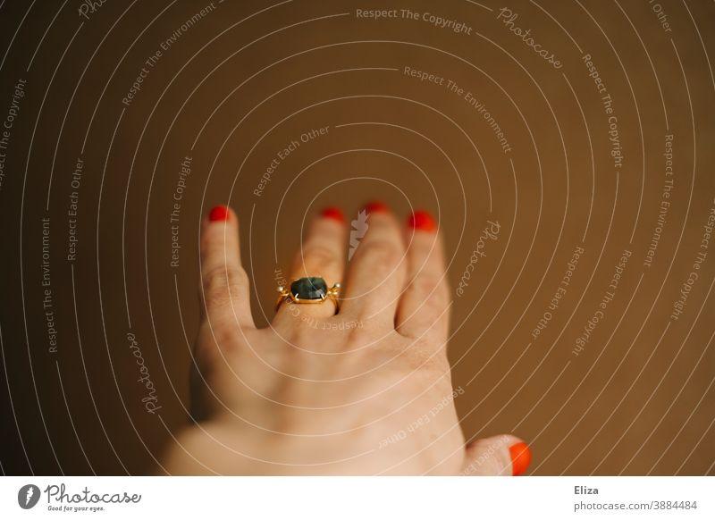 Linke Hand einer Frau mit einem Ring am Ringfinger Verlobungsring Schmuck verlobt weiblich lackierte Nägel Finger feminin