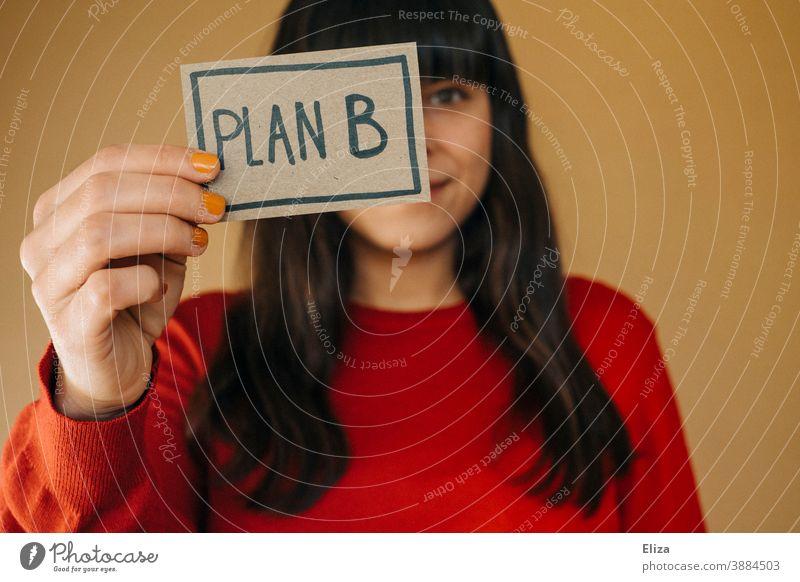 Eine dunkelhaarige Frau in rotem Pullover hält ein Schild mit der Aufschrift Plan B hoch Flexibilität Alternative planen Business Mensch zweiter Bildungsweg