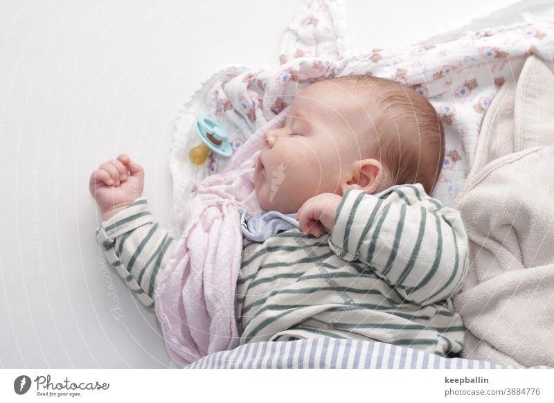 Baby schläft auf einem Bett mit Decken Kleinkind Schnuller Tuch schlafen Mittagsschlaf friedlich ruhig träumen Gesicht