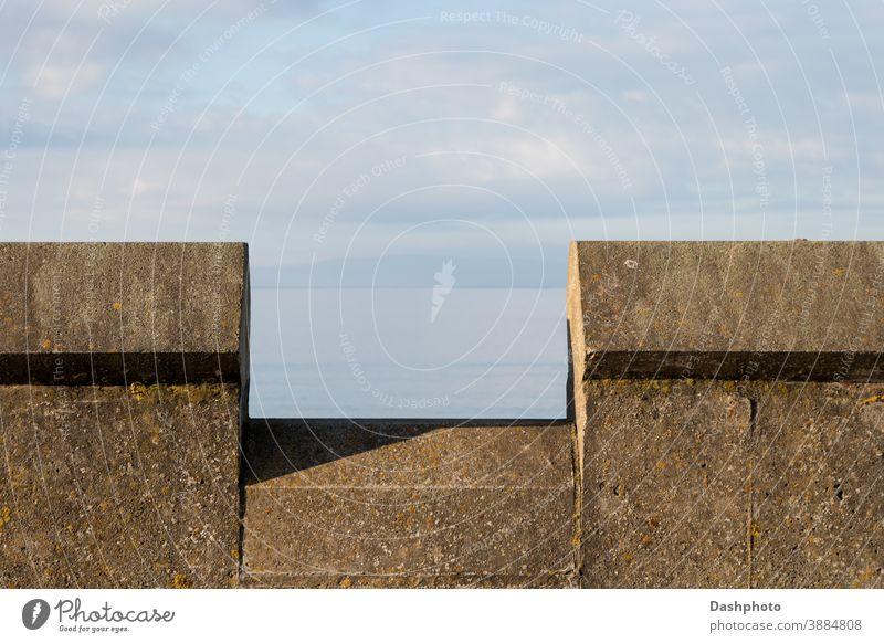 Brüstungsmauer am Strand an einem Küstenstandort Wand Stein Steine braun Algen Moos Schatten Konstruktion Architektur Mauerwerk Maurerhandwerk alt Ansicht