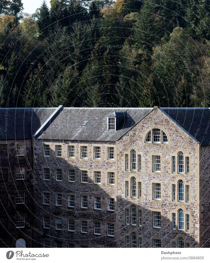 Altes stillgelegtes Mühlengebäude in New Lanark Village Schottland in der Herbstsonne Dorf konvertiert Gebäude Stein Mauerwerk Maurerhandwerk Schatten Baum