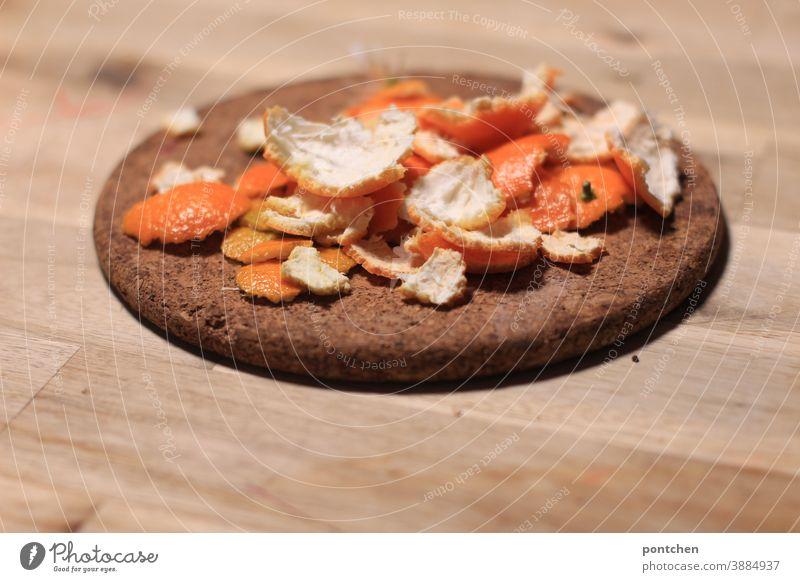 Mandarinenschalen liegen auf einem Untersetzer aus Kork auf einem Holztisch. Winter. Vitamin c mandarinenschalen geschält obst frucht gesund ernährung kork