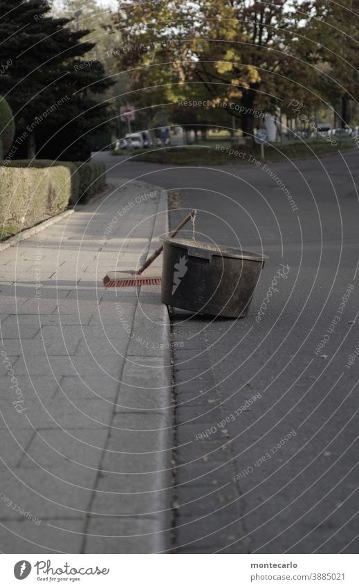 Besen und Laubpott stehen wartend auf der Straße im Pott Starke Tiefenschärfe Tag Textfreiraum rechts Außenaufnahme Besenstiel Borsten Holz spießig Gärtner grau