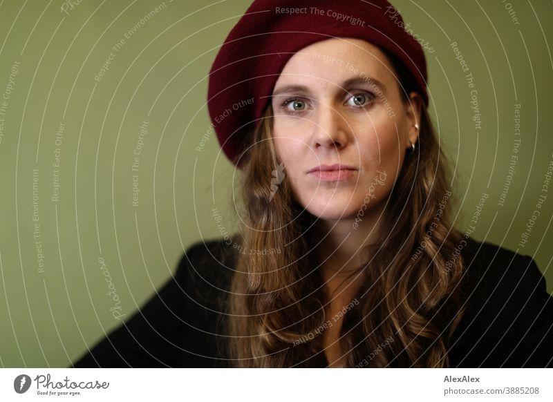 Portrait einer jungen Frau mit Hut vor einer grünen Wand schlank schön brünett lange Haare Gesicht schlau emotional sehen schauen Blick direkt natürlich