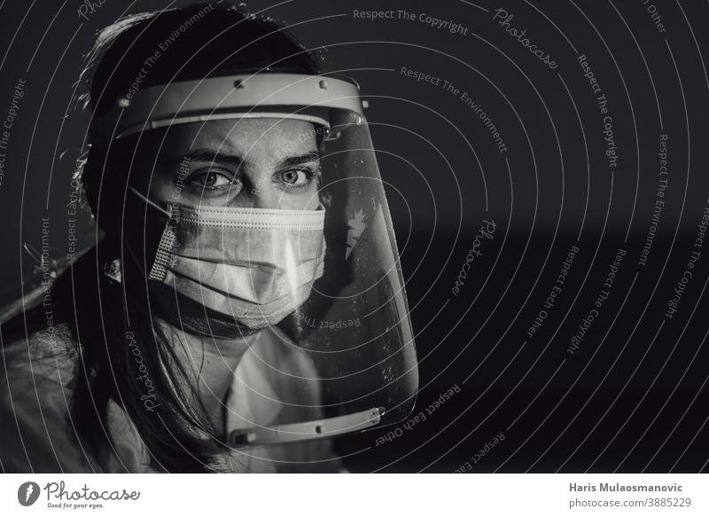 hart arbeitende Ärztin, Gesundheitshelferin mit Gesichtsschutz und Maske in schwarz-weiß schwarzer Hintergrund Brasilien Korona-Epidemie Corona-Virus covid-19