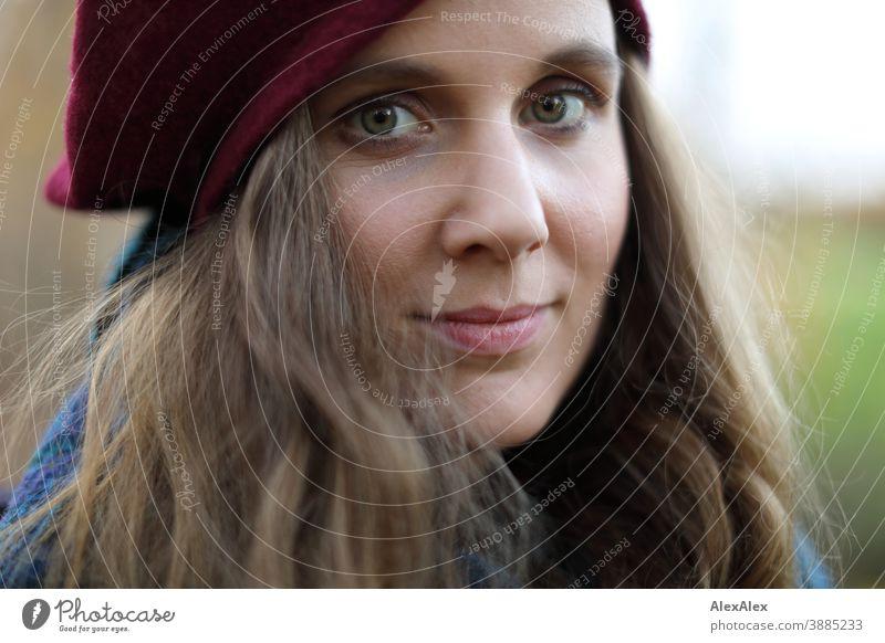 Nahes Portrait einer jungen Frau mit Hut schlank schön brünett lange Haare Gesicht schlau emotional sehen schauen Blick direkt natürlich hellhäutig blass