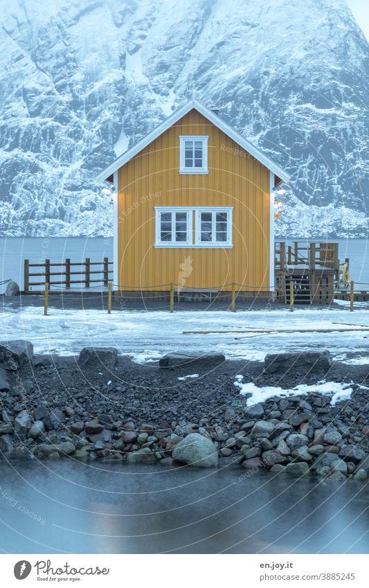 Gelbe Hütte am Fjord in Reine auf den Lofoten gelb Haus Rorbuer Fischerhütte Ferienhaus Norwegen Reinefjorden Winter Schnee Skandinavien Dämmerung Abend Berg