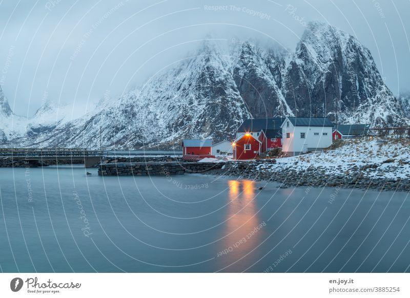 Rote und weiße Hütten in Reine auf den Lofoten zur blauen Stunde Norwegen Reinefjorden Skandinavien blaue Stunde Abendsonne Rorbuer Haus Häuserzeile Ferienhaus